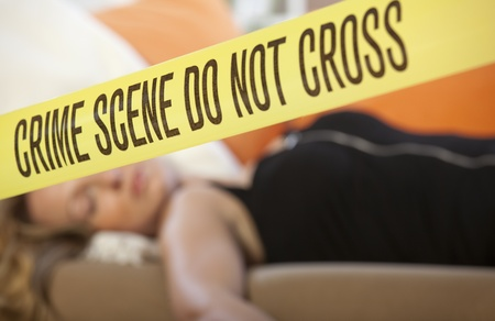 Close up crime scene investigation police boundary tape with dead woman in background Stock Photo - 8630539