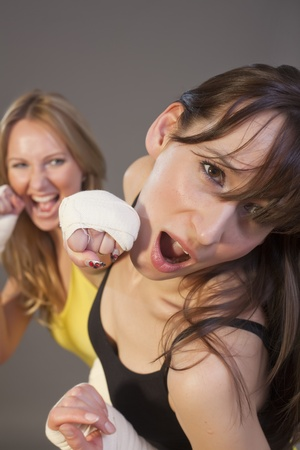 struggle: two women in bare knuckles fist fighting over grey background Stock Photo