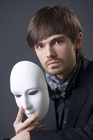 elegant man in depression holding white mask  photo