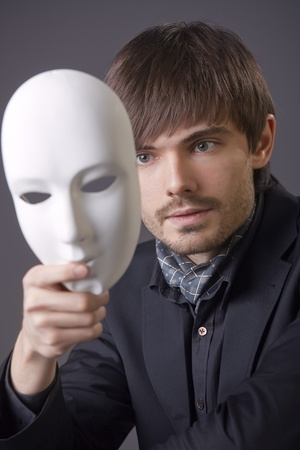 theatre masks: fashion man hiding his face under white mask Stock Photo