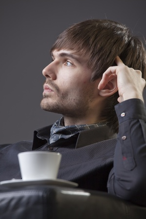 thinking man sitting in the chair with cup coffee Stock Photo - 8814714