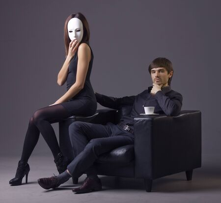 arrogant man and masked woman sitting in the chair over grey background