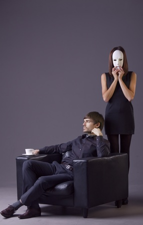 couple conflict - woman holding white mask and arrogant man with cup coffee photo