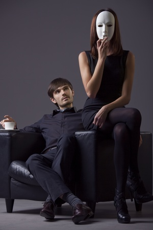 masked woman and proud man sitting on the chair - focus on woman photo