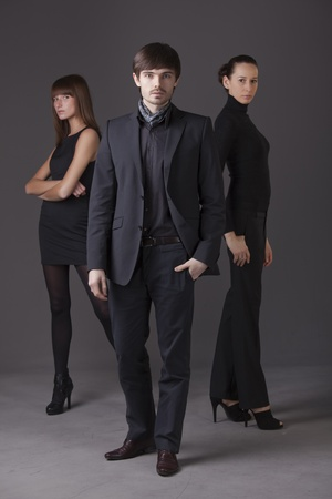 fashion people - one man and two women posing over grey background