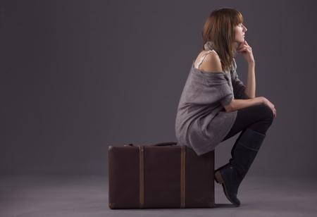 mujer con maleta: mujer triste sentada en la maleta antigua y esperando