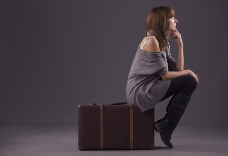 sad woman sitting on old suitcase and waiting photo