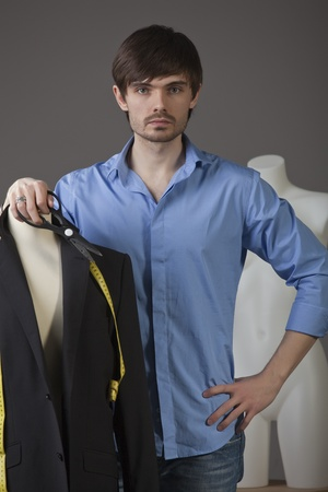 portrait of male tailor with two mannequins photo