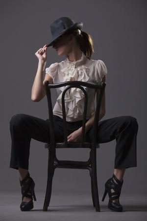 t�nzerin: T�nzerin mit Hut sitzend auf dem Stuhl �ber grau hintergrund