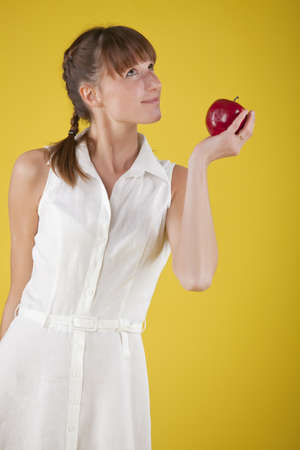 imagining: woman holding apple fruit and imagining over yellow background Stock Photo