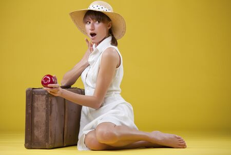 surprised retro woman in hat with old suitcase on the ground photo