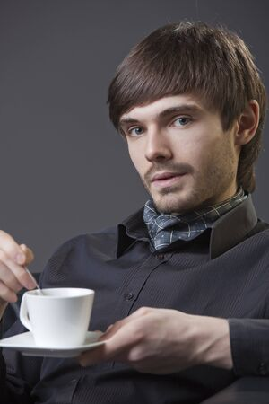 businessmann holding a cup of coffee over grey background photo