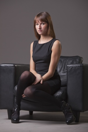 portrait of young woman sitting in the leather chair photo