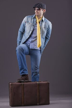 man in denim clothes and sunglasses standing on suitcase photo