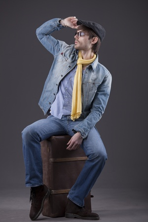 fashion man in denim clothes sitting on old suitcase