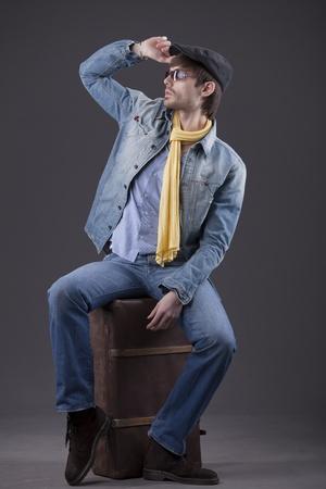 vestidos antiguos: hombre de moda en ropa de mezclilla sentado en la maleta antigua