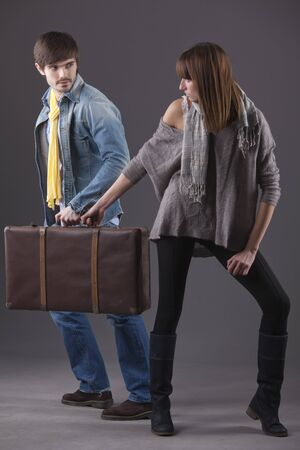 young man and woman fight over suitcase photo