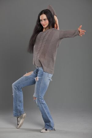 dancing woman in jeans over grey background photo