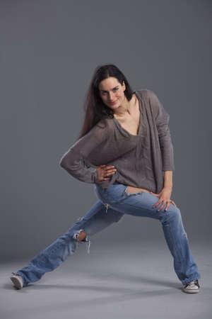 portrait of woman dancer in denim jeans over grey background photo