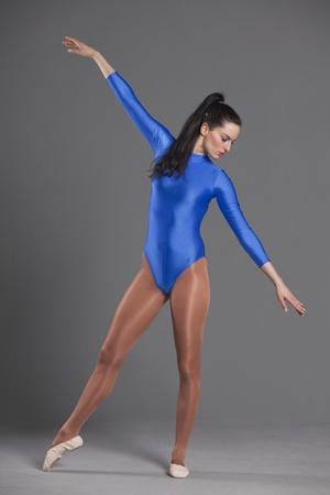 turnanzug: Frau in gymnastischen �bungen �ber grau hintergrund Trikot Lizenzfreie Bilder