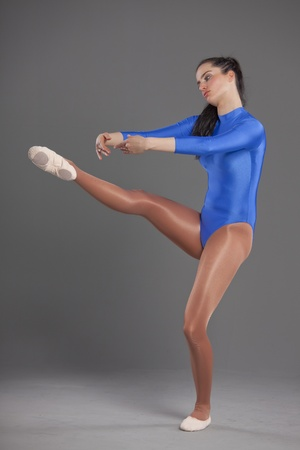 woman in blue leotard doing ballet exercises photo