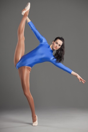 female dancer in leotard with one leg raised in splits pose on grey back ground photo