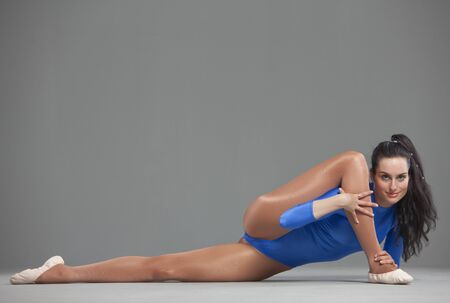 lycra: woman in blue leotard in extreme splits pose over grey background Stock Photo
