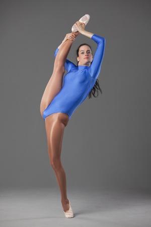 lycra: female gymnast in extreme splits pose over grey background Stock Photo