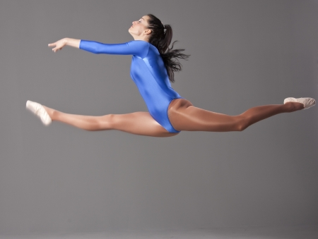 leotard: female gymnast doing splits in the air over grey background