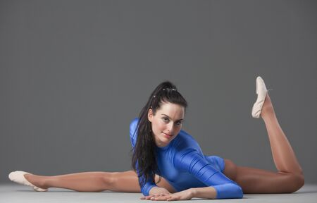 female gymnast in blue leotard resting on the ground photo