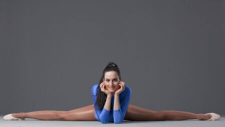 smiling female gymnast in splits pose on the ground photo