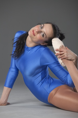 ballet dancer in blue leotard doing stretching exercises photo
