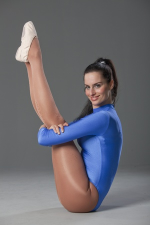 female gymnast in blue leotard holding her both legs photo