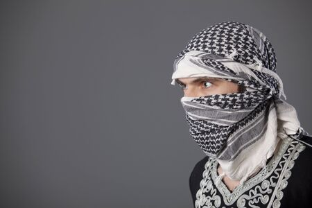 terrorists: portrait of islamic man in headscarf over grey background Stock Photo