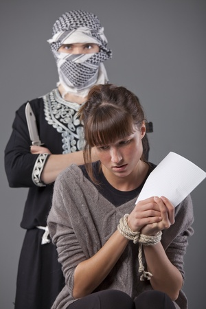 helpless: helpless and tied up female hostage and terrorist with knife Stock Photo