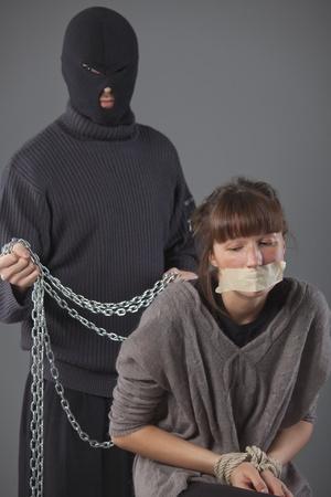 hijacker: mujer secuestrada indefensa y secuestrador con cadena en segundo plano Foto de archivo