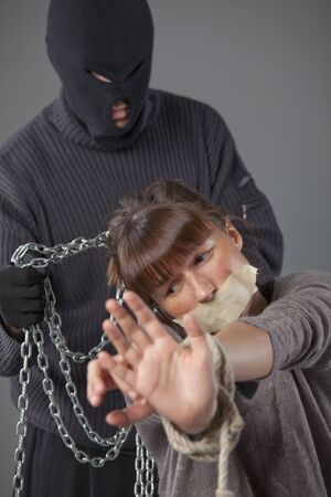 prisoner woman: kidnapper with chain and helpless female victim