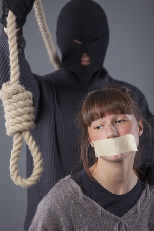 tied woman: hangman with noose and female victim over grey background