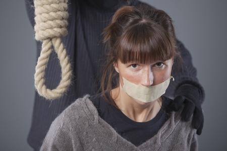 ahorcado: mujer secuestrada y ahorcado con soga sobre fondo gris