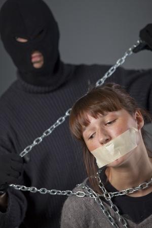 hijacker: la mujer secuestrada, atada y secuestrador con cadena en segundo plano Foto de archivo