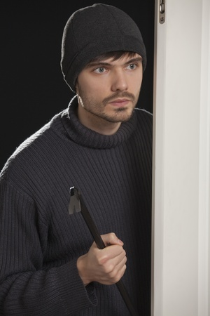 thief with crowbar standing at the door and looking into the room photo
