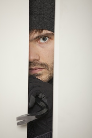 Burglar with crowbar breaks into a house Stock Photo