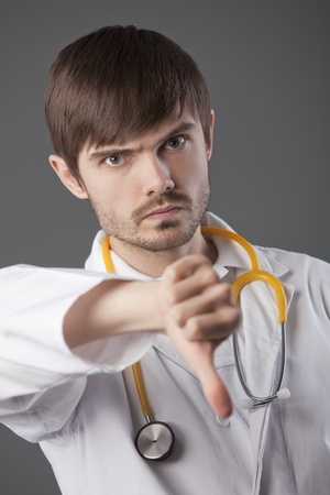 unhappy male doctor with thumbs down sign