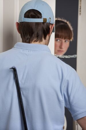 woman opening the door and seeing the thief with crowbar photo