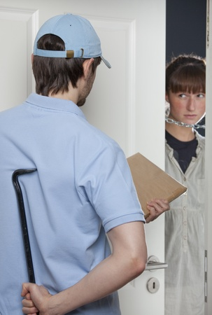 intruder: fake delivery man holding a small package and crowbar while woman opening the door Stock Photo