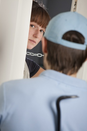 woman opening the door and seeing a man with crowbar photo