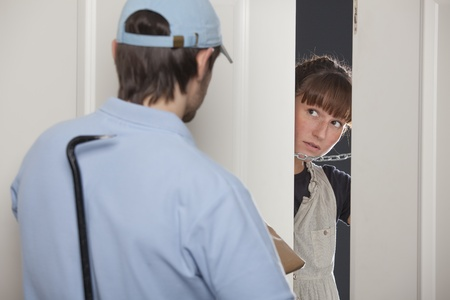 criminal delivery man with crowbar and package - woman opens the door  photo