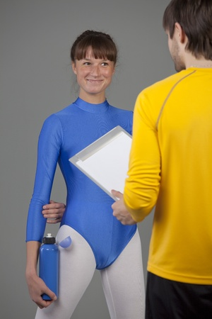 leotard: woman in blue leotard with personal fitness trainer