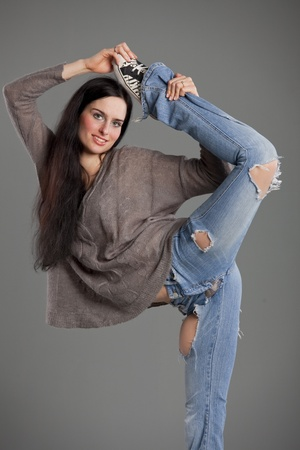 ripped jeans: modern dancing - hip hop woman stretching her leg over head Stock Photo
