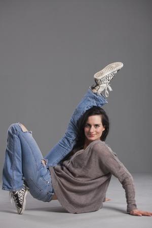 hip hop dancer in denim jeans over grey background photo